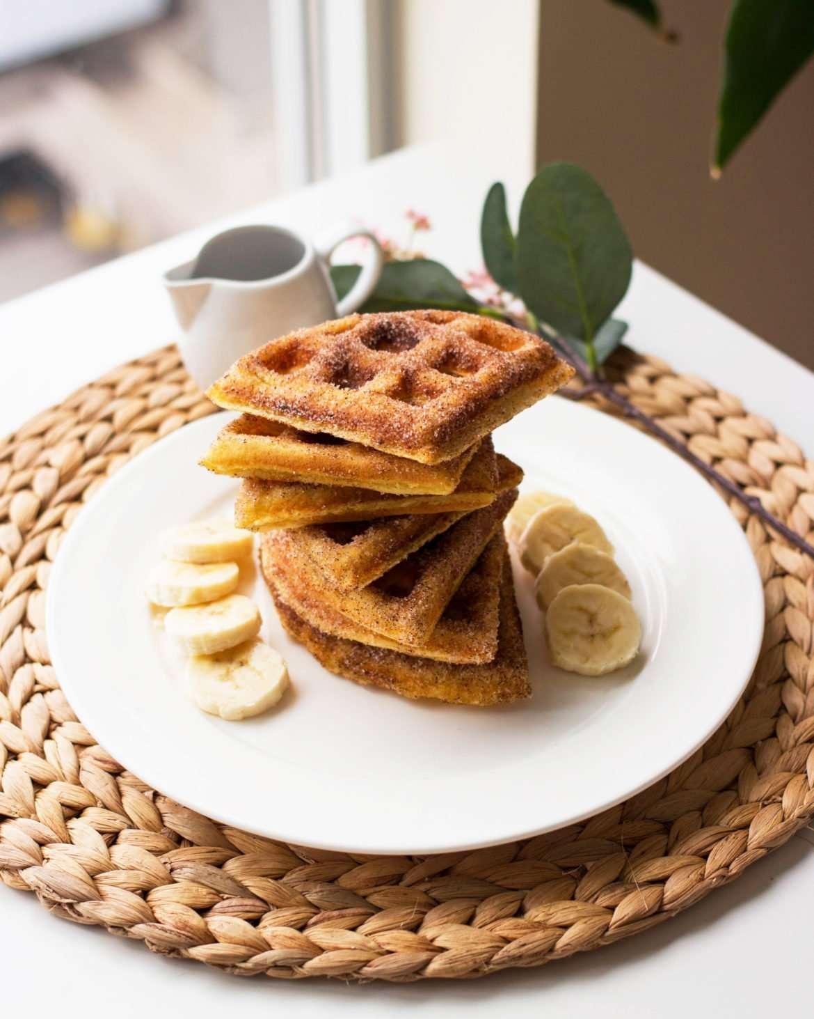 photo of churro waffles dipped in cinnamon sugar
