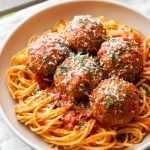 Italian meatballs served over a bowl of spaghetti